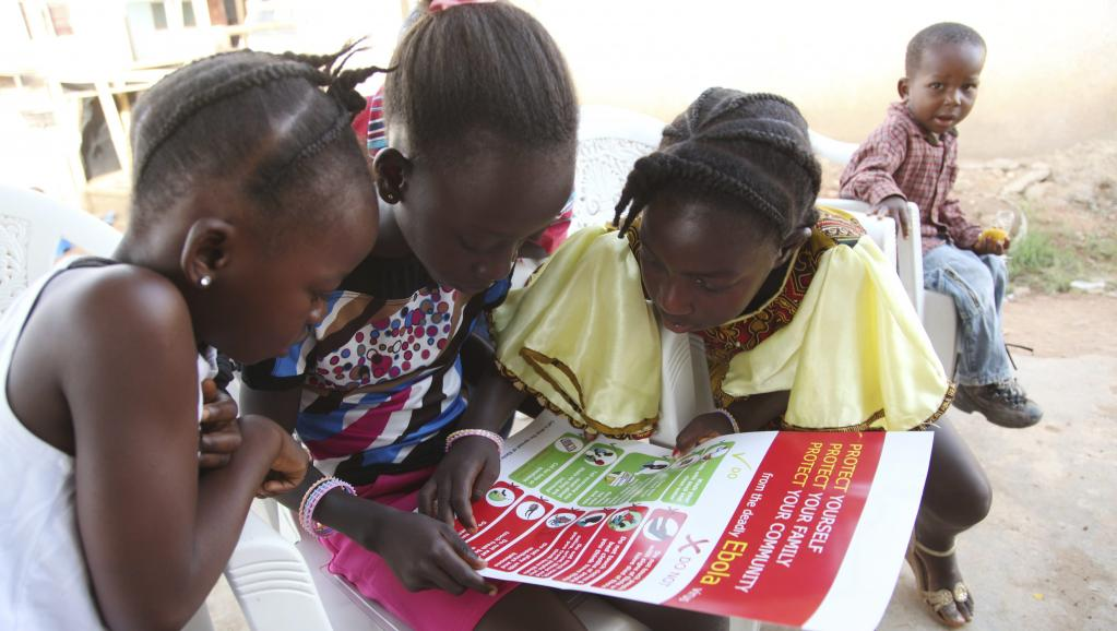 Au Liberia, des enfants lisent les documents sur l'Ebola distribués par l'Unicef. Unicef