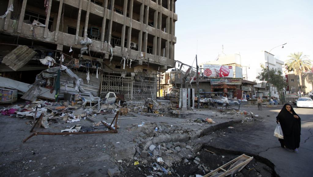 Une femme passe près d'un cratère causé par une attaque à la voiture piégée, à Bagdad, ce mercredi 13 août 2014. Deux attaques à la voiture piégée ont tué 12 personnes dans la capitale irakienne. Les jihadistes espèrent gagner aussi cette ville.