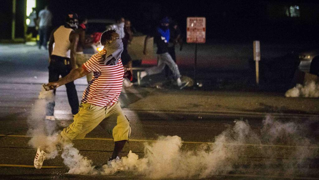 Un manifestant renvoie une grenade lacrymogène envoyée par les forces de l'ordre, à Ferguson, ce dimanche soir à quelques heures du couvre-feu (5h00 TU) REUTERS/Lucas Jackson