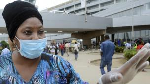 Une femme portant masque et gant de protection à l'aéroport de Murtala Muhammed de Lagos avant la confirmation d'un troisième cas Ebola dans le pays.