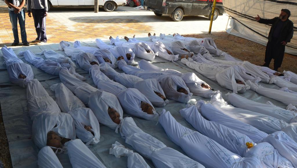 Des activistes syriens inspectent des corps de civils tués, selon eux, par des agents chimiques, le 21 août, dans la banlieue de Damas. REUTERS/Bassam Khabieh