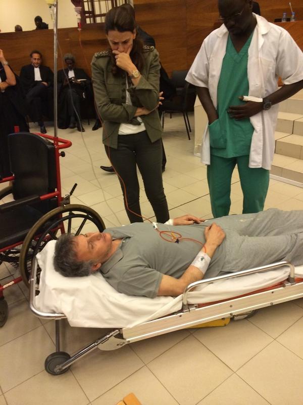 Photo: Bibo Bourgi couché sur un lit d'hôpital en plein procès