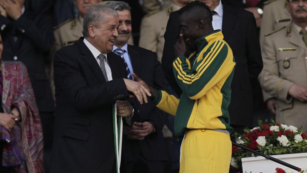 Le joueur Albert Ebossé avec le Premier ministre algérien à la fin d'un match en mai 2014. REUTERS/LOUAFI LARBI