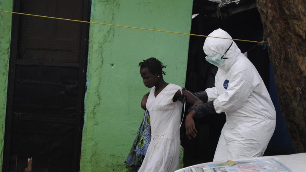 A Monrovia, au Liberia, une femme suspectée d'être atteinte du virus d'Ebola est accompagnée par un soignant vers une ambulance, le 15 septembre 2014.
