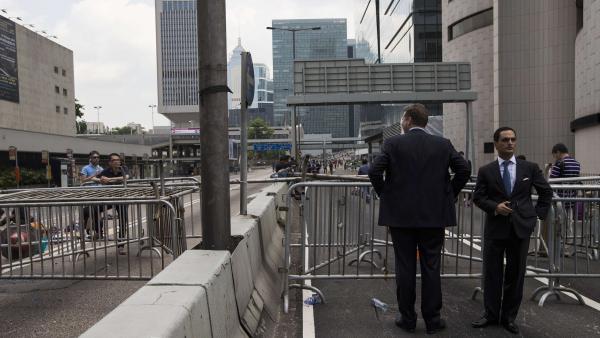 Des hommes d'affaires, devant une route bloquée par les manifestants pro-démocratie, en plein centre du quartier de la finance, à Hong Kong, ce lundi 29 septembre, au matin. REUTERS/Tyrone Siu