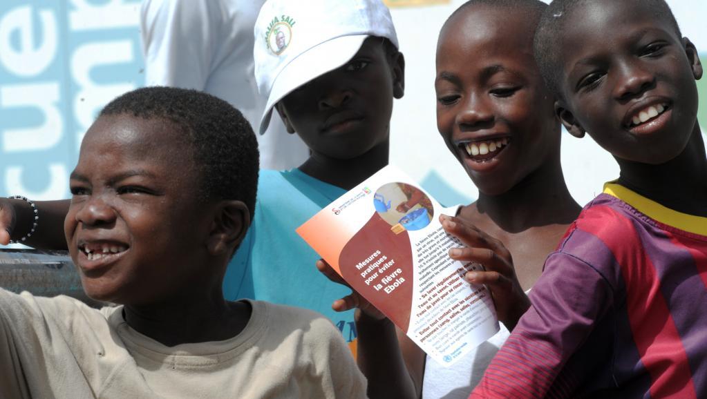 Des garçons lisent une brochure sur la prévention du virus Ebola dans les faubourgs de Dakar, au Sénégal. AFP PHOTO / SEYLLOU