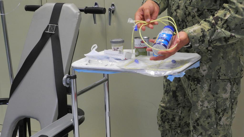 Un médecin militaire montre le matériel utilisé à Guantanamo pour forcer l'alimentation des prisonniers grévistes de la faim, le 7 août 2013. AFP PHOTO/Chantal Valery
