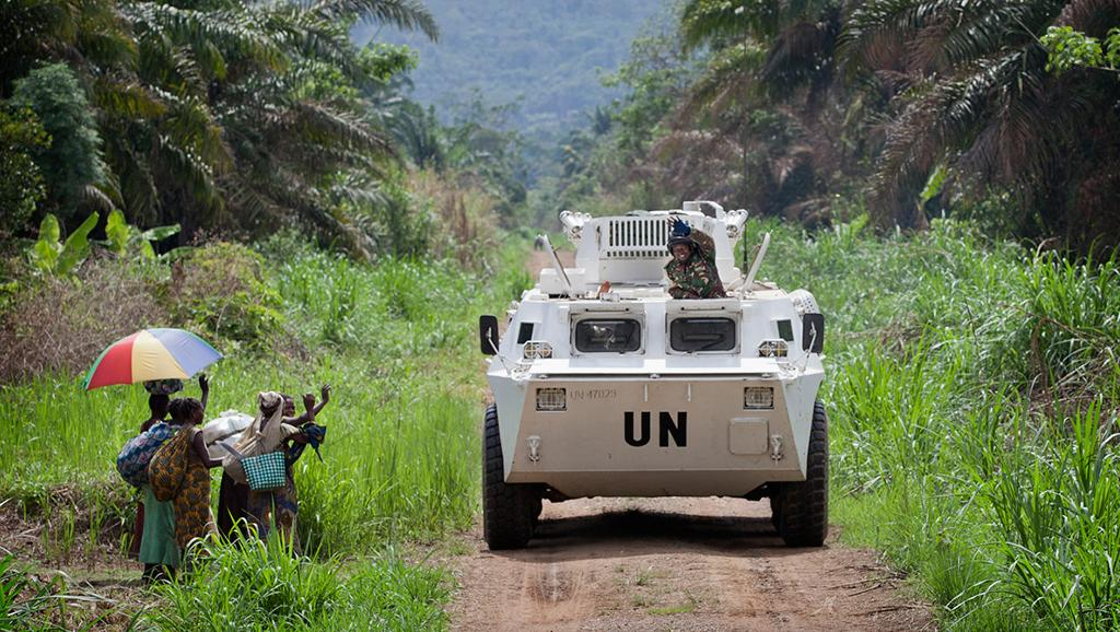 Des membres de la population locale, saluant le passage d'un véhicule blindé de transport de troupes de la Monusco, qui se dirige dans la région de Beni, province du Nord Kivu en RDC, le 13 mars 2014.