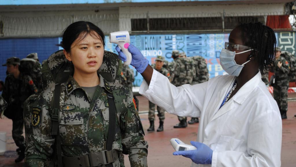 Prise de température d'une jeune femme membre du convoi de renforts chinois dans la lutte contre Ebola. Aéroport Roberts à Monrovia, le 15 novembre 2014. REUTERS/James Giahyue