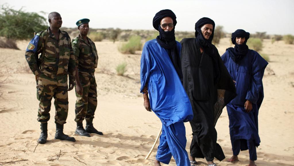 Des soldats maliens aux côtés de Touaregs dans un village près de Tombouctou, en juillet 2014. MALI-UN/ REUTERS/Joe Penney/Files