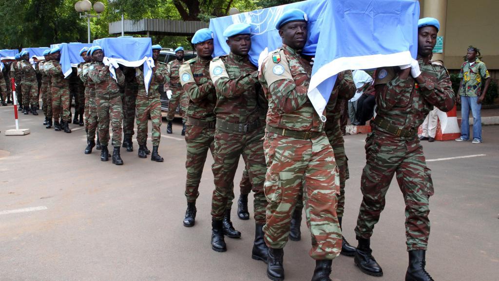 A Bamako, le 7 octobre, les cercueils -recouverts du drapeau de l'ONU- de 9 casques bleus nigériens sont portés par leurs collègues de la Minusma. AFP/Habibou Kouyaté