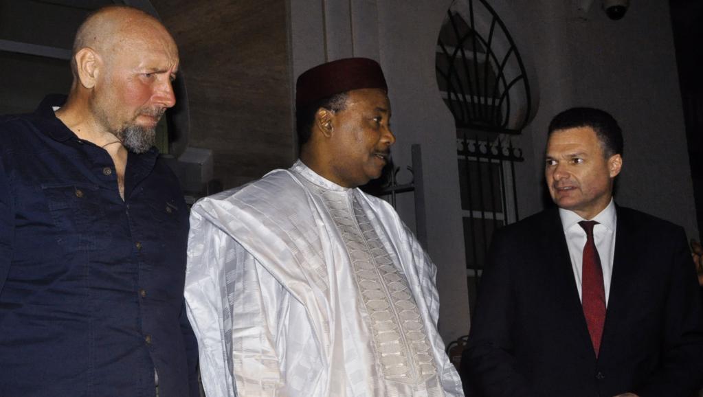 Serge Lazarevic (g) peu de temps après son arrivée au Niger aux côtés du président Issoufou et de l'ambassadeur français au Niger, le 9 décembre. AFP PHOTO / HAMA BOUREIMA