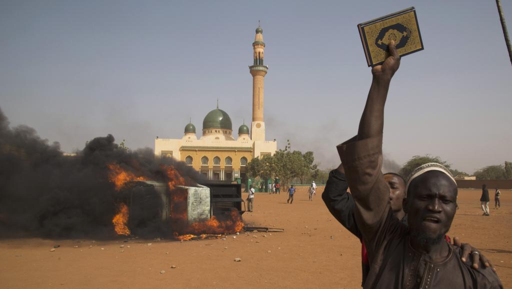 Un homme brandit un Coran, sur fond de véhicule en feu et d'une mosquée, à Niamey, où de violentes manifestations se sont déroulées le 17 janvier en réaction à la publication de caricatures dans le journal Charlie Hebdo. REUTERS/Tagaza Djibo