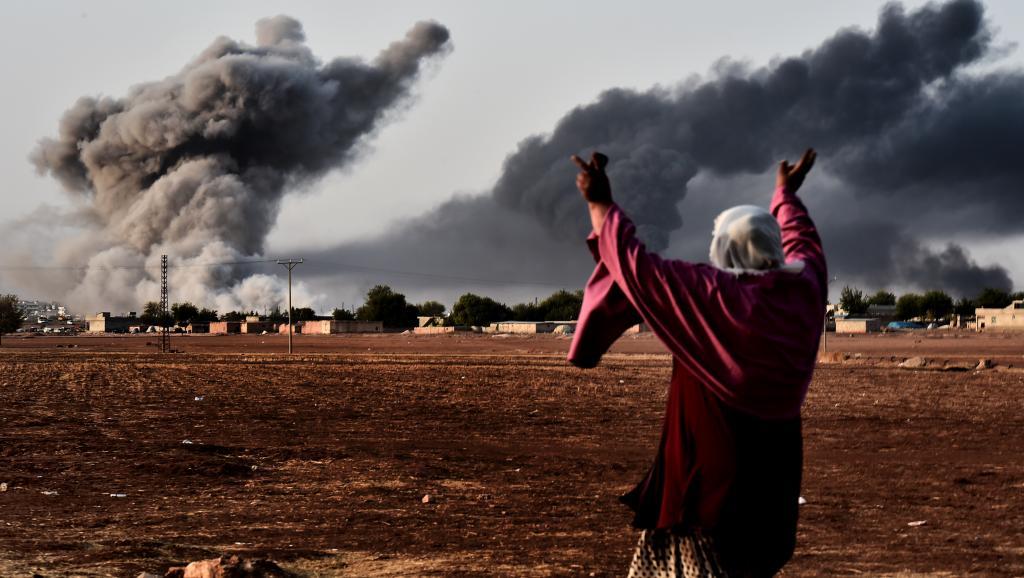 A la frontière turque, une femme contemple la ville kurde syrienne de Kobane après une frappe de la coalition, le 13 octobre 2014. Le bilan de ces raids aériens est au menu de la réunion de Londres, ce 22 janvier.