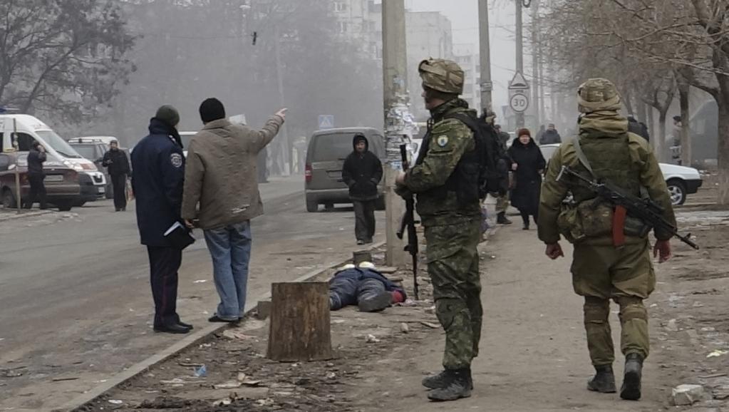 Des militaires ukrainiens en faction dans une rue de Marioupol, près du corps d'une vicitime des bombardements, le 24 janvier 2015. REUTERS/Nikolai Ryabchenko