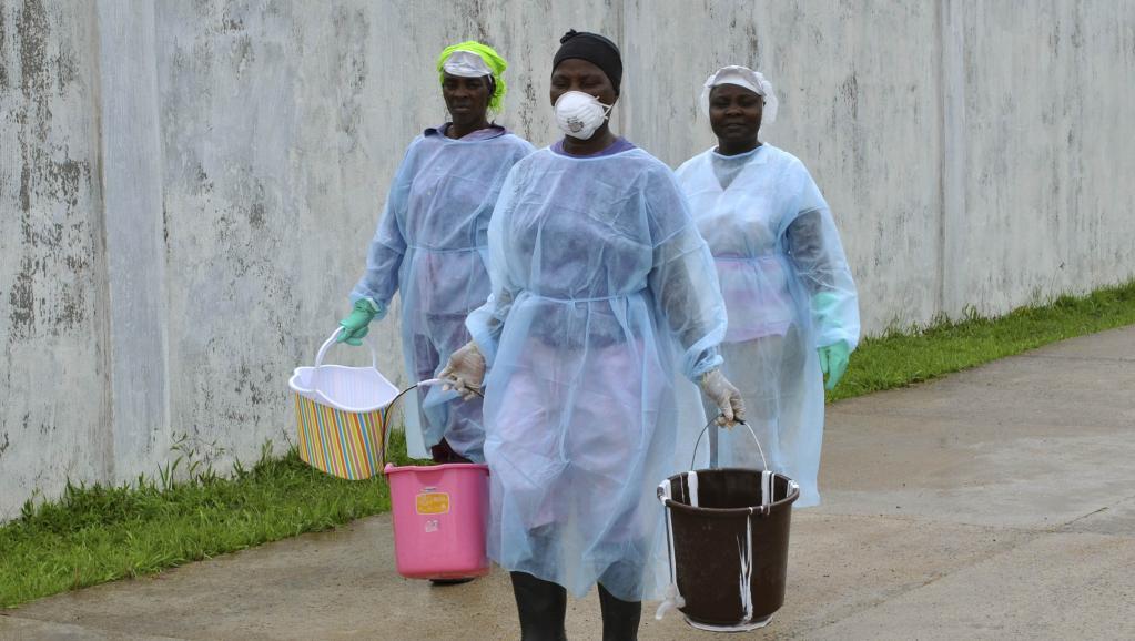 Des volontaires transportent des seaux de désinfectant jusqu'au centre de traitement Ebola, à Monrovia, le 25 septembre 2014.
