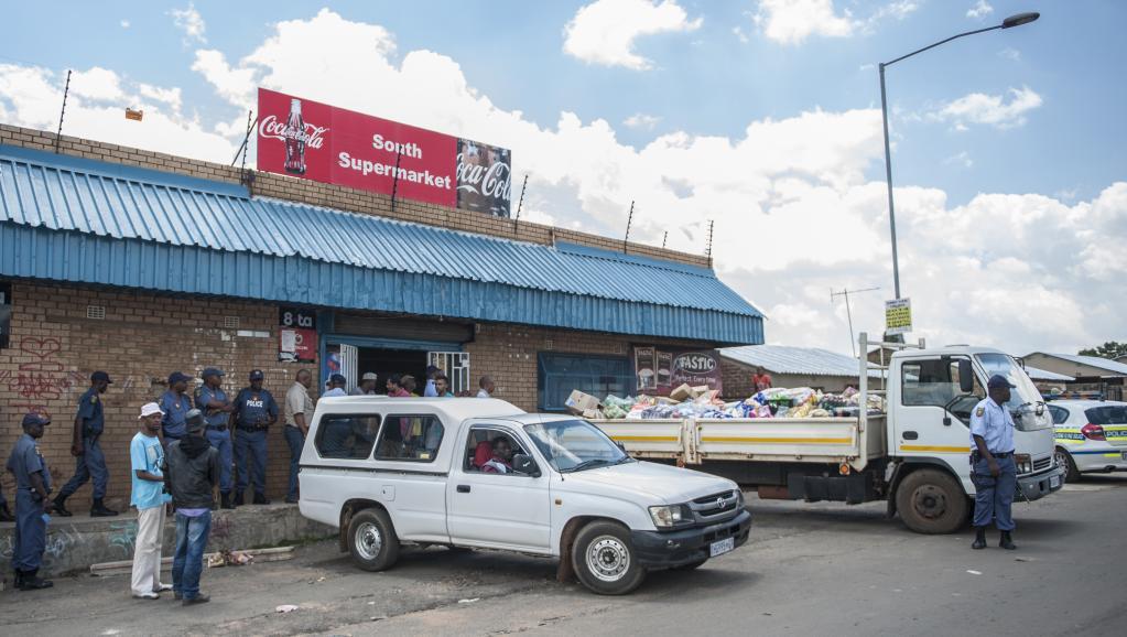 Des policiers sud-africains postés, le 23 janvier, devant un magasin tenu par des étrangers pour prévenir les vols à Kagiso, un bidonville à l'ouest de Johannesburg. AFP PHOTO/STEFAN HEUNIS