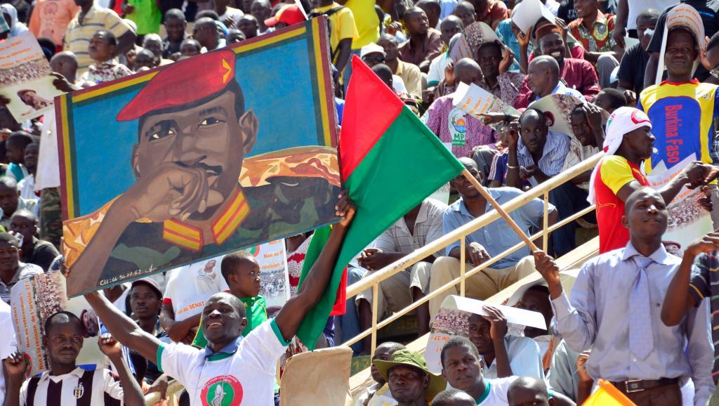 Un membre de l'opposition brandit un portrait de Thomas Sankara, le père de la révolution burkinabè, lors d'un meeting en novembre 2014. AHMED OUOBA / AFP