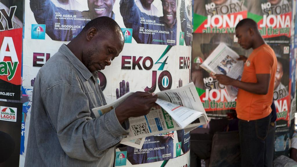 Des hommes lisent des journaux devant des affiches électorales, à Lagos, le 30 mars 2015. REUTERS/Joe Penney