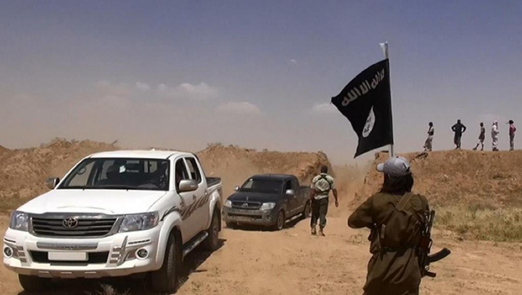 Un membre du groupe Etat islamique brandit un drapeau de son organisation, près de la frontière irako-syrienne. ALBARAKA NEWS / AFP
