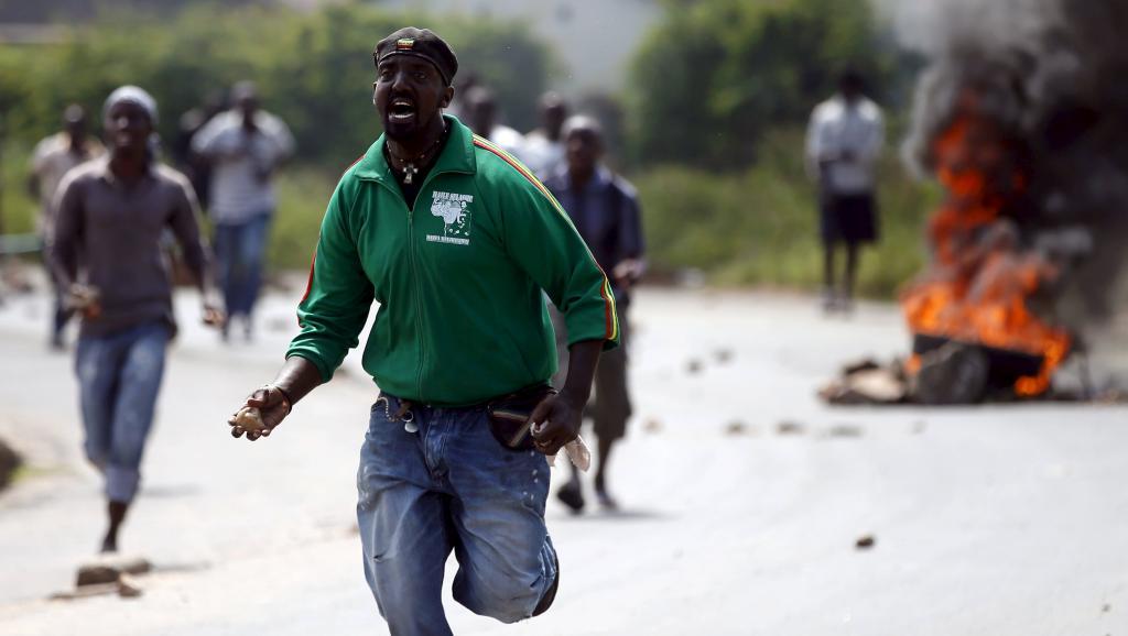 Des protestants jettent des pierres contre des policiers, le 21 mai à Bujumbura. REUTERS/Goran Tomasevic