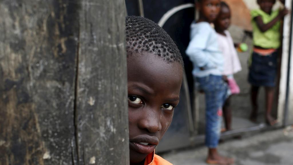 Un enfant regarde des policiers détruire une barricade dans les rues de Bujumbura, le 30 mai 2015. REUTERS/Goran Tomasevic