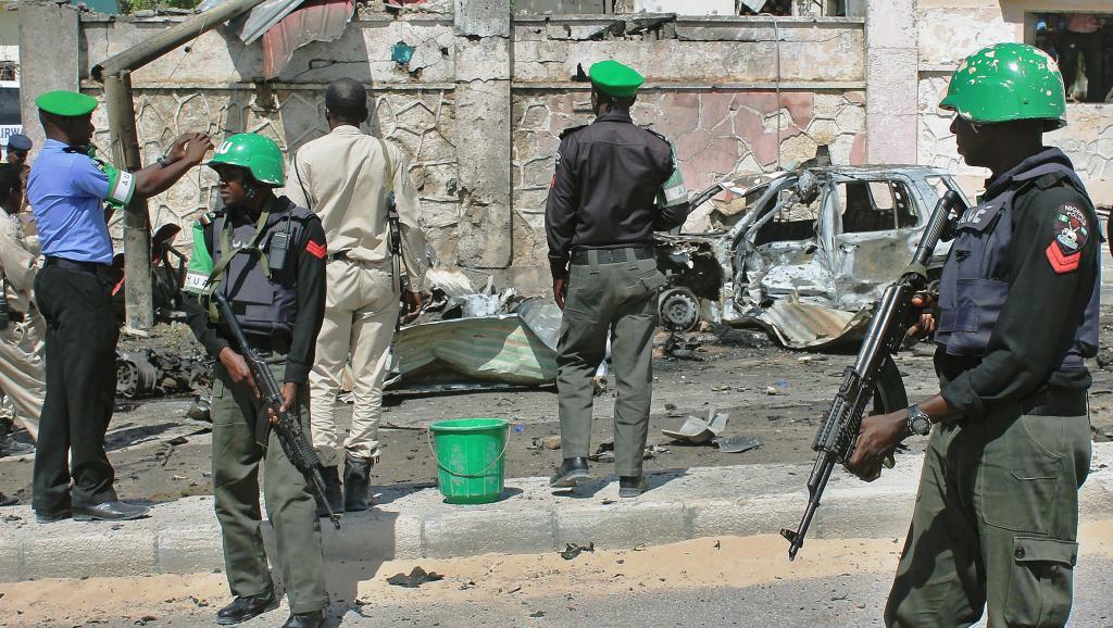 Des soldats de l'Amisom sur le site d'un attentat, devant les portes hautement sécurisées de l'aéroport de Mogadiscio, le 3 décembre 2014. AFP PHOTO/ABDULFITAH HASHI NOR