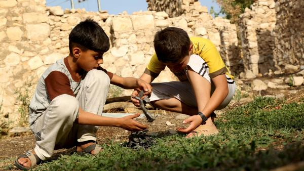 Deux enfants tiennent un morceau de débris de bombe lâché par l'aviation turc sur le village d'Amadiya en Irak du nord. REUTERS/Ari Jalal