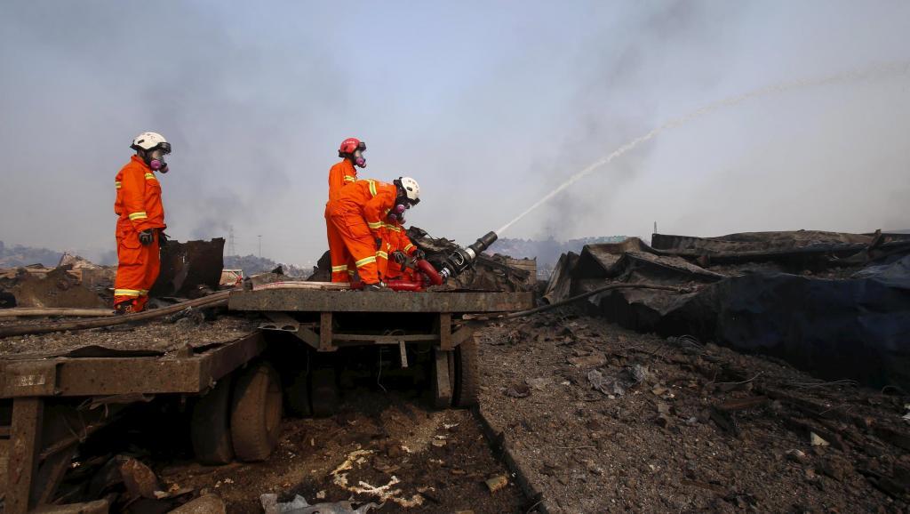 Les pompiers sont toujours en action ce samedi 15 août sur le site de la catastrophe industrielle, porteurs de masques à gaz en raison des émanations toxiques. REUTERS/China Daily