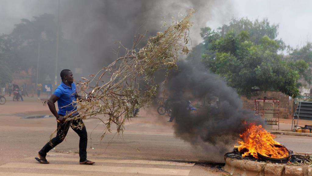 Un manifestant lance des branchages dans un brasier, à l'intersection de plusieurs rues, à Ouagadougou ce 18 septembre. REUTERS/Joe Penney