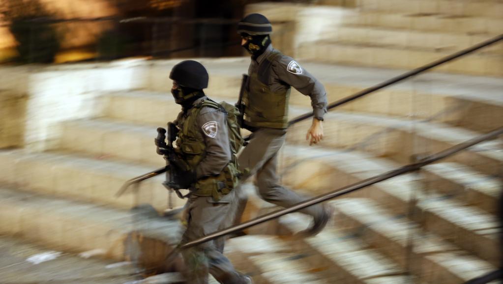 Des policiers se rendent sur les lieux d'une agression au couteau, à Jérusalem, le 3 octobre 2015. AFP PHOTO / AHMAD GHARABLI