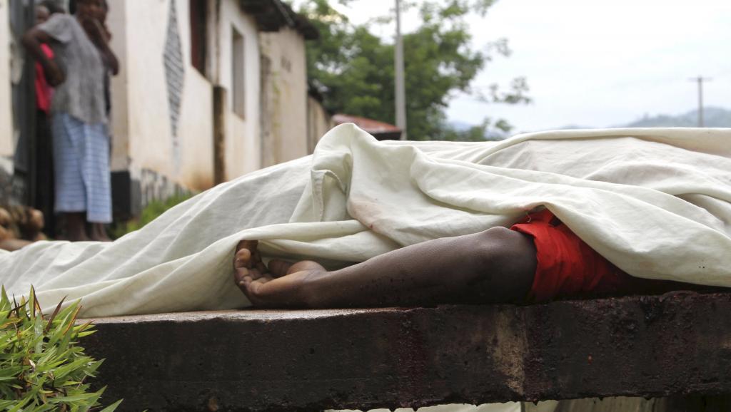 Des habitants regardent le corps d'un homme tué dans le quartier de Nyakabiga, à Bujumbura, le 12 décembre 2015. Les affrontements de vendredi à Bujumbura, la capitale du Burundi, ont fait 87 morts, a annoncé l'armée. © REUTERS/Jean Pierre Aime Harerimana